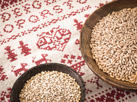 Bowls of spelt grains and buckwheat grains on cross stitch doily - DISF001469
