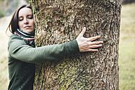 Woman hugging a big tree trunk - GEMF000154