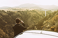 Portugal, Azores, man taking picture of landscape with bridge - ONF000797