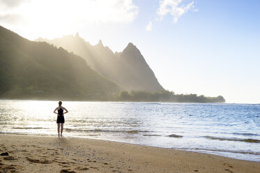 USA, Hawaii, Hanalei, woman standing on Haena Beach, View to Na Pali Coast in the evening light - BRF001115