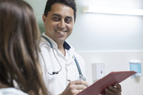 Smiling doctor taking notes while listening to patient - BZF000099