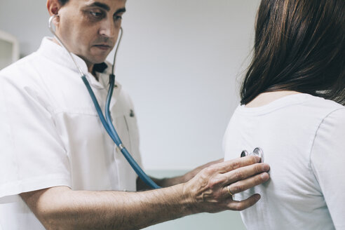 Doctor listening to patient's back with stethoscope - BZF000113