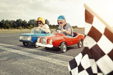 Two boys in pedal cars crossing finishing line on race track - EDF000159
