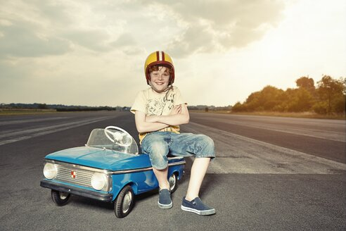 Smiling boy with pedal car on race track - EDF000168