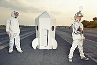 Two boys dressed up as spacemen standing at cardboard rocket - EDF000147