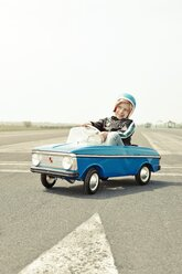 Smiling boy in pedal car on race track - EDF000176