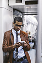 Businessman with smartphone and earphones hearing music on the subway train - EBSF000489