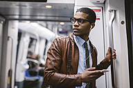Businessman with smartphone and earphones hearing music on the subway train - EBSF000493