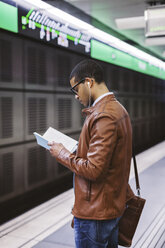 Spain, Barcelona, businessman standing at underground station platform reading book - EBSF000497