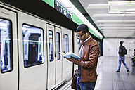 Spain, Barcelona, businessman standing at underground station platform reading book - EBSF000500