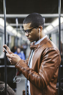 Portrait of businessman with smartphone and earphones hearing music on the subway train - EBSF000507