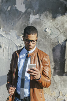 Businessman with smartphone wearing leather jacket and glasses - EBSF000512