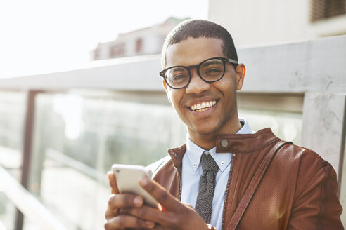 Portrait of smiling businessman with smartphone wearing leather jacket and glasses - EBSF000518
