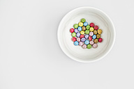 Pastel colored sweets in a white bowl on white background - MELF000055