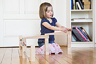 Little girl crouching on floor playing with marble run - LVF003162