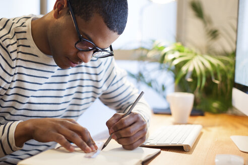 Young creative man sitting at desk writing in his notebook - EBSF000542