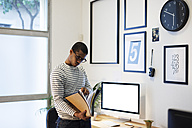 Young creative man with files in his home office - EBSF000548