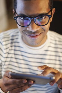 Portrait of smiling young man using mini tablet - EBSF000551