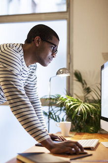 Young creative man working at computer in his home office - EBSF000553