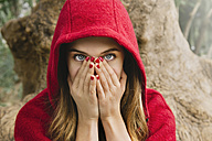 Frightened woman wearing red hood covering face with her hands - GEMF000173