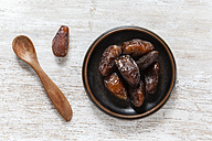 Wooden spoon and bowl of Medjooll dates on wood - EVGF001546