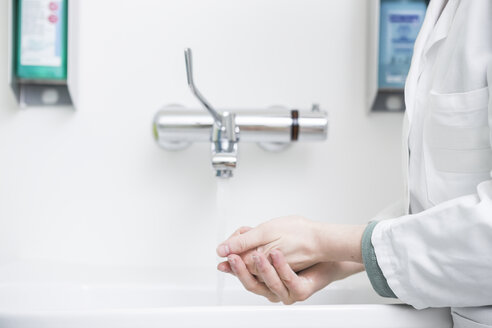 Young lab technician washing hands - DISF001635