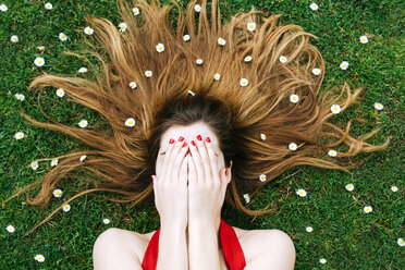Woman lying on grass in spring with hands on face and flowers on hair - GEMF000178