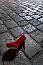Red high heel lying on cobblestone pavement at night - EJWF000754