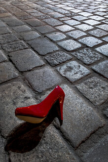 Red high heel lying on cobblestone pavement at night - EJWF000754
