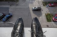 Man standing on ledge above street - EJWF000756