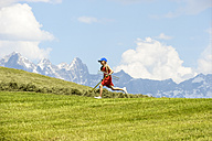 Austria, Flachau, girl running with rake on a harvested meadow - HHF005291