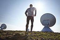Germany, Raisting, young man jogging at ground station - KDF000703
