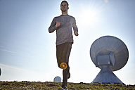 Germany, Raisting, young man jogging at ground station - KDF000710