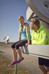 Germany, Raisting, young jogger couple having a rest at ground station - KDF000713