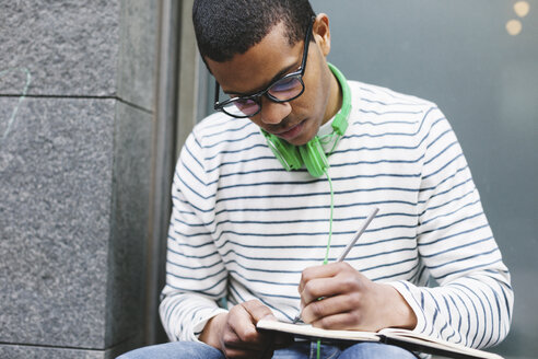 Young man with green headphones sitting outside writing something in his notebook - EBSF000561