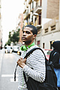 Spain, Barcelona, young man with green headphones and backpack on street - EBSF000571