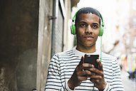 Spain, Barcelona, portrait of smiling young man hearing music with green headphones on street - EBSF000574