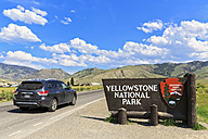 USA, Yellowstone National Park Sign at entrance, car on road - FO007998