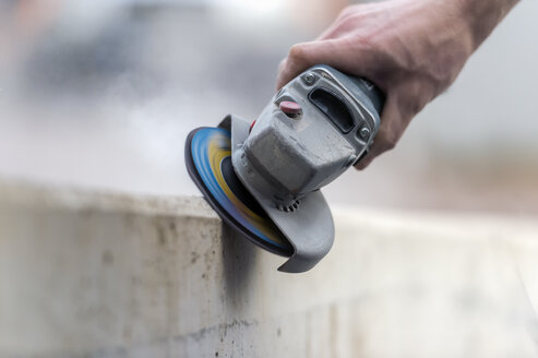 Craftsman using grinder at concrete block - FRF000241