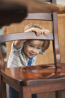 Portrait of smiling little boy hiding behind chair - SELF000026