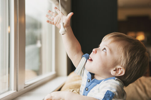 Little boy reaching out for window blind cord - SELF000027