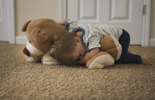 Tired little boy sleeping on the floor with bear - SELF000044