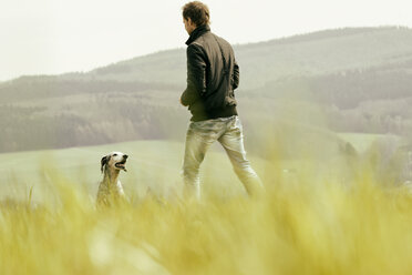 Man with dog on meadow - ONF000811