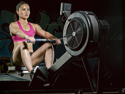 Young woman exercising at rowing machine - MADF000188