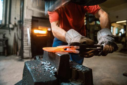 Senior blacksmith working in hammer mill - HHF005328