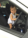 Baby standing on driver's seat holding steering wheel - DRF001567