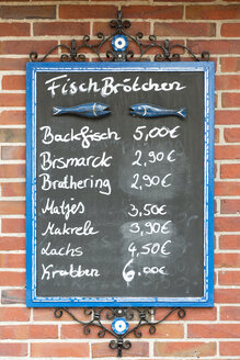 Germany, Spiekeroog, Blackboard with prices of various fish sandwiches - KEBF000116