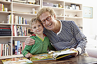 Grandfather and grandson reading children's book together - RHF000754
