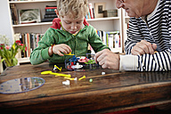 Grandfather and grandson assembling toy clock - RHF000756