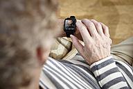 Senior man sitting in armchair using smartwatch - RHF000771
